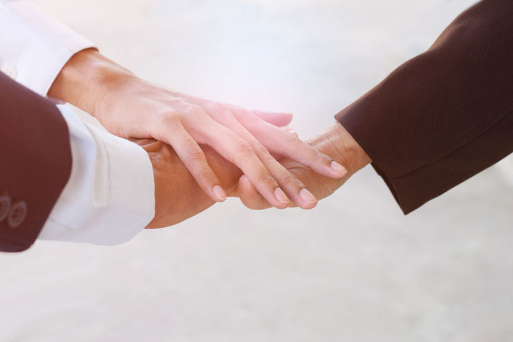 Cropped image of colleagues stacking hands against white background