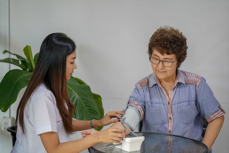 Doctor examining patient at table