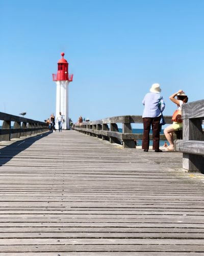 Lighthouse and ladies People Wooden Tourism Summertime Bridge Lighthouse_lovers Lighthouse Architecture Built Structure Direction Sky Building Exterior Real People Lighthouse Clear Sky Day