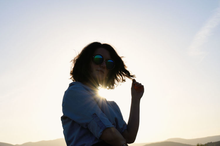Midsection of woman with sunglasses against sky during sunset