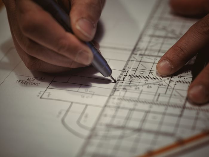 Cropped hands of architect drawing blueprint