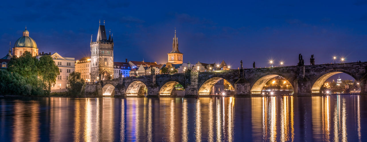 The Charles Bridge of Prague Arch Bridge Architecture Being A Tourist Bridge - Man Made Structure Built Structure Capital Cities  Charles Bridge City Lights City Lights At Night Connection Neighborhood Map Illuminated Night Night Lights Nightphotography Outdoors Panorama Prague Praha Reflection River Tourism Travel Destinations Water light and reflection