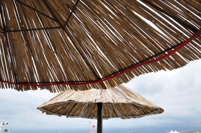 Calm Relaxing Travel Beach Beach Umbrella Break Cloud - Sky Day Joy Low Angle View Nature No People Outdoors Parasol Pattern Protection Sea Security Shade Sky Summer Sunshade Tourism Umbrella Wood - Material