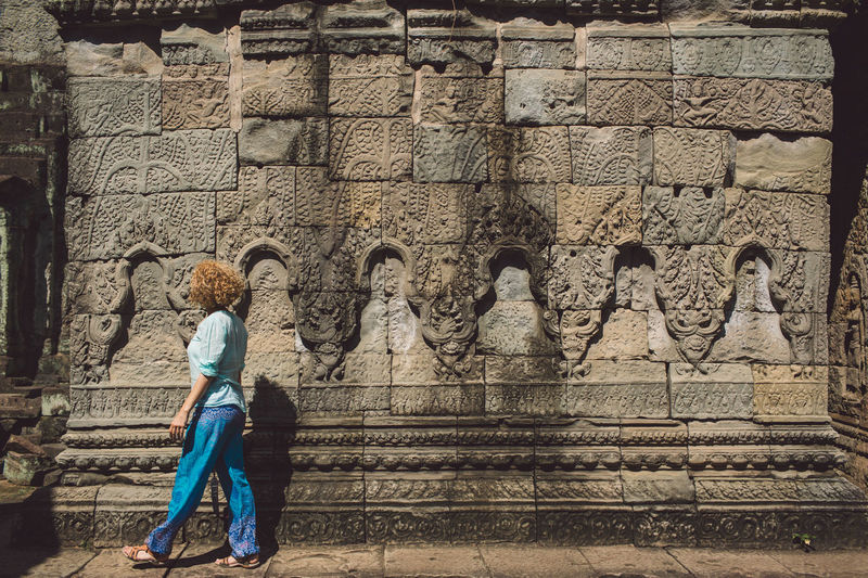 Side View Of Woman Walking By Old Ruin Angkor Wat