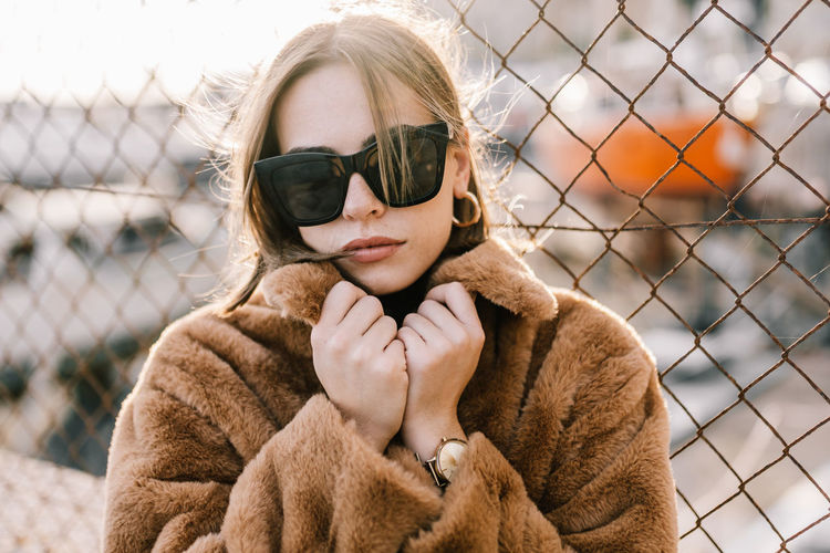 Portrait of young woman in sunglasses during winter