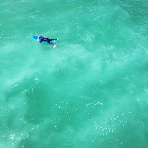 Surfer Swimming in Emerald Ocean The Color Of Sport