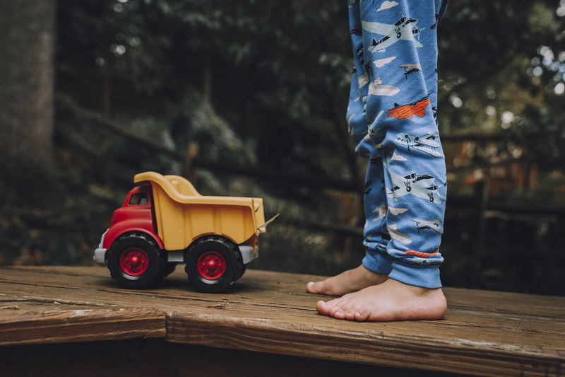 Low section of child standing by toy car on wooden floor
