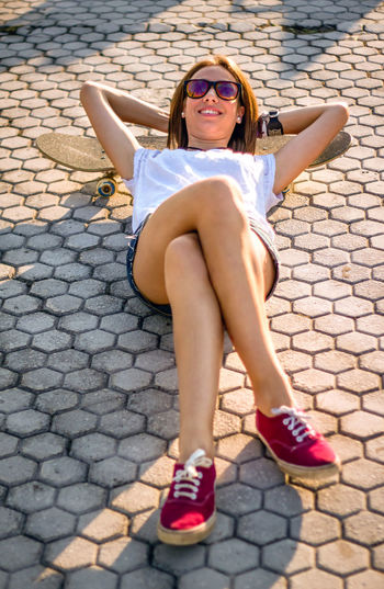 Portrait of a young woman sitting on cobblestone