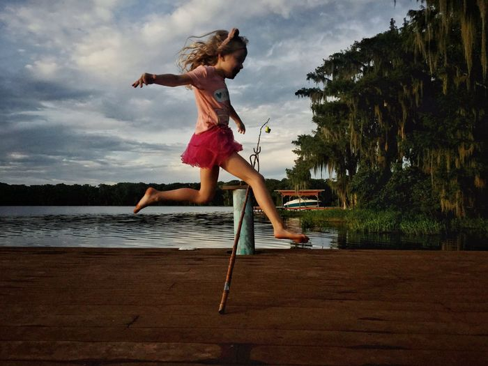 Girl jumping over fishing rod at lakeshore against sky