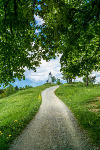 Footpath Amidst Grassy Field Leading To Church Of St Primoz Against Cloudy Sky