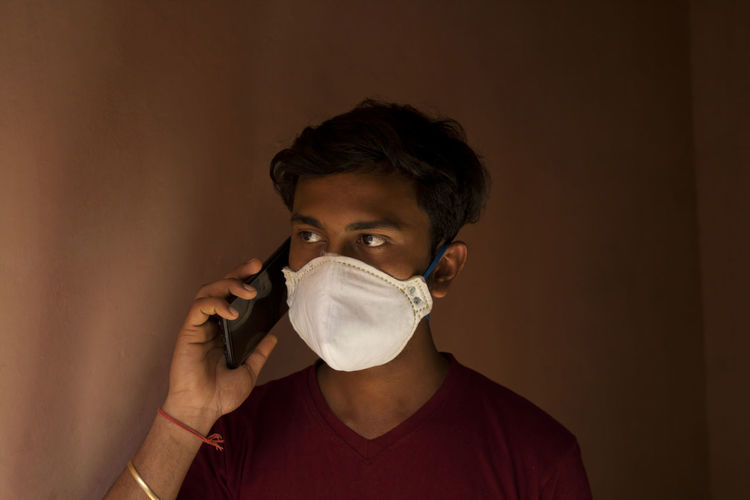 Close-up of young man wearing flu mask talking on phone against wall at home