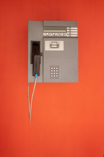 Cable Close-up Colored Background Communication Connection Copy Space Electricity  Indoors  Landline Phone Network Connection Plug No People Pay Phone Payphone Phone Cord Power Supply Red Single Object Studio Shot Technology Telephone Telephone Receiver Wall - Building Feature