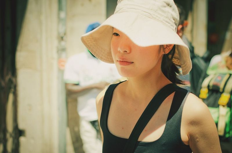 Close-up of young woman wearing hat on sunny day