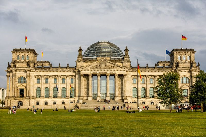 People at reichstag building against cloudy sky