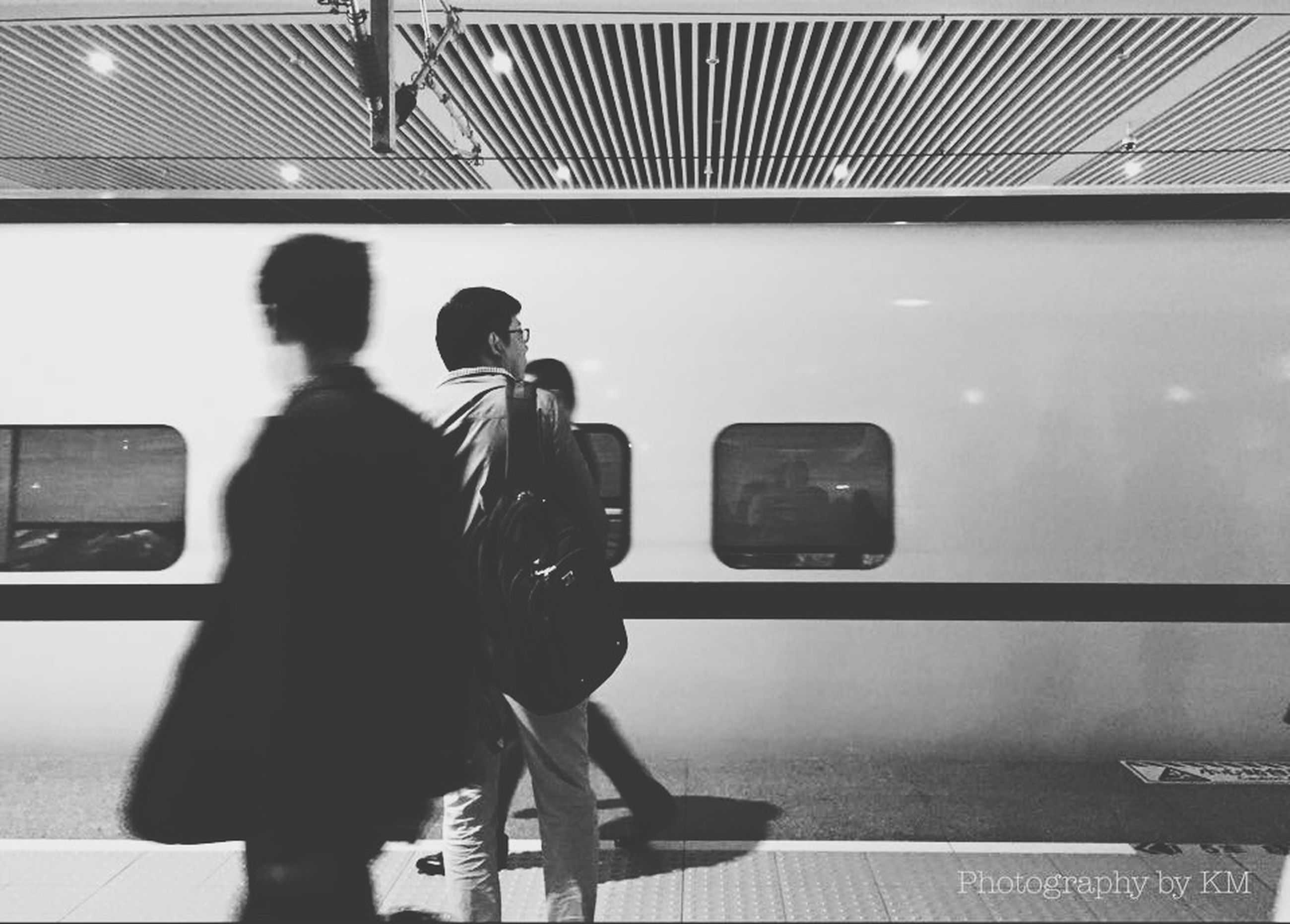 indoors, men, transportation, technology, lifestyles, rear view, communication, leisure activity, full length, travel, public transportation, mode of transport, wireless technology, person, photography themes, passenger, connection