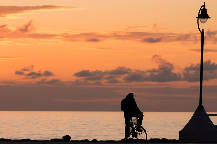 A biker in the sunset Sunset Silhouette Orange Color Sky Sea Nature Beauty In Nature Cloud - Sky Tranquility One Person Horizon Over Water Outdoors Real People