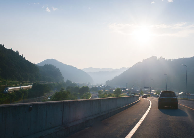 On the roads of Yamagata. Japan. Japan Yamagata,Japan Beauty In Nature Car Crash Barrier Day Direction Fog Lens Flare Mode Of Transportation Motor Vehicle Mountain Mountain Range Nature No People Outdoors Road Scenics - Nature Sign Sky Sunbeam Sunlight The Way Forward Tranquility Transportation