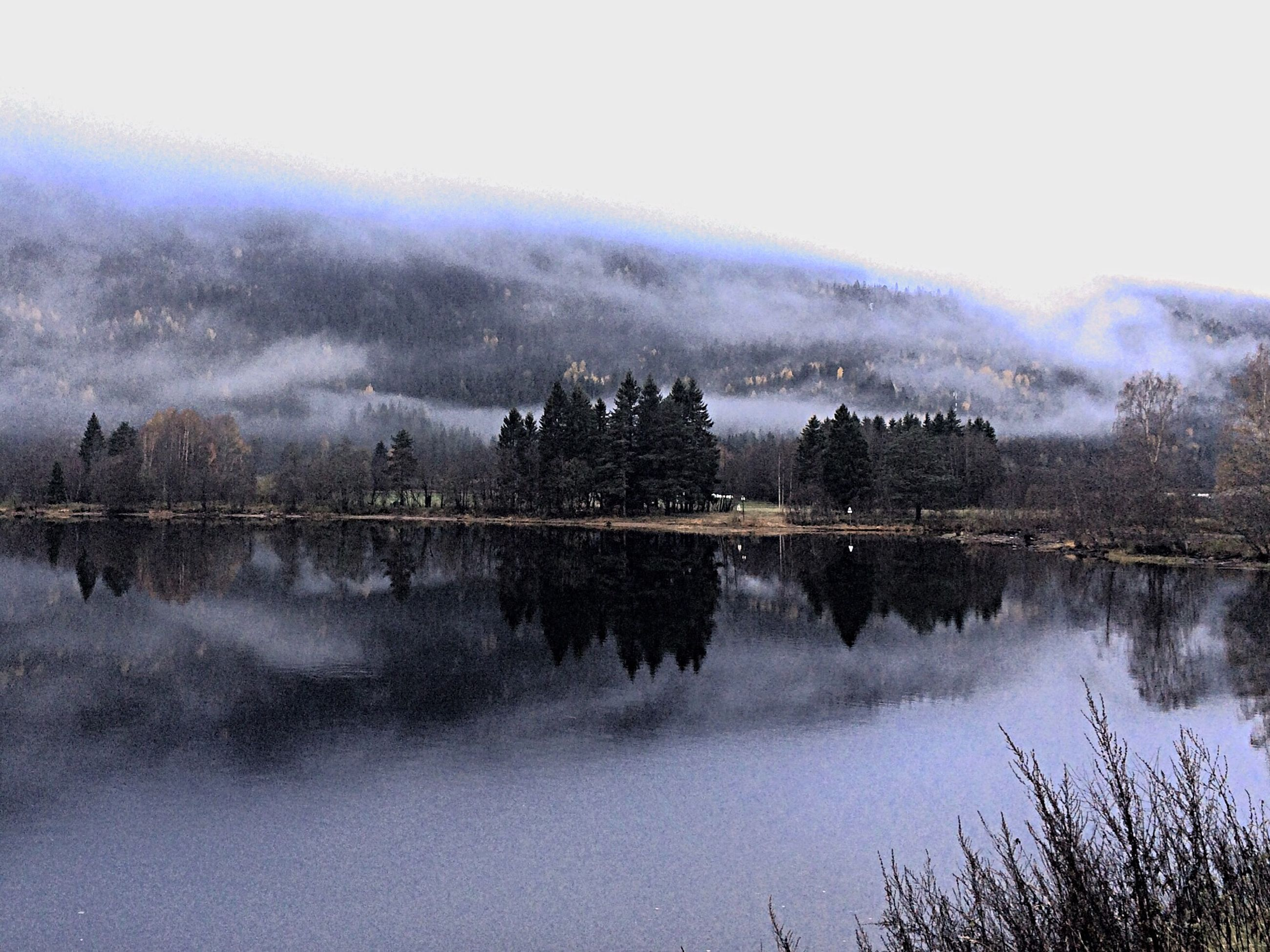 reflection, water, lake, tranquil scene, tranquility, scenics, beauty in nature, tree, standing water, fog, sky, waterfront, nature, weather, symmetry, calm, idyllic, river, foggy, outdoors