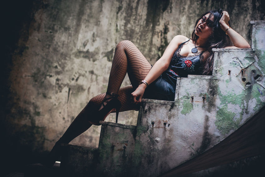 Abandoned Architecture Beautiful Woman Casual Clothing Communication Contemplation Damaged Day Dirty Full Length Hairstyle Indoors  Lifestyles One Person Real People Relaxation Sadness Sitting Wall - Building Feature Women Young Adult Young Women