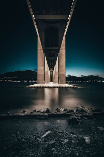 Low angle view of bridge over river against sky at night
