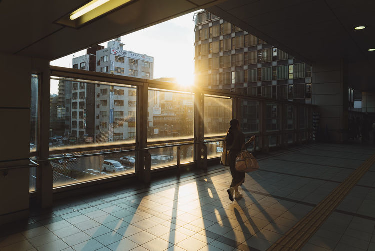 The Street Photographer - 2018 EyeEm Awards Architecture Building Building Exterior Built Structure City Flooring Full Length Glass - Material Lens Flare Lifestyles Nature Office Building Exterior One Person Outdoors Real People Sky Sun Sunlight Sunset Tiled Floor Window