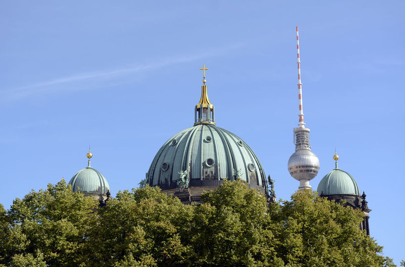 Low angle view of fernsehturm and berlin cathedral by trees against sky