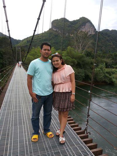 Full length portrait of couple standing over river on footbridge