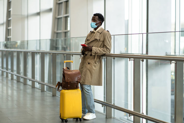 Afro traveler man stands in airport terminal, wear face mask, waiting for flight and boarding