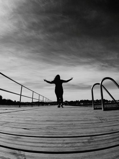 Rear view of silhouette young woman with arms outstretched standing on pier against sky