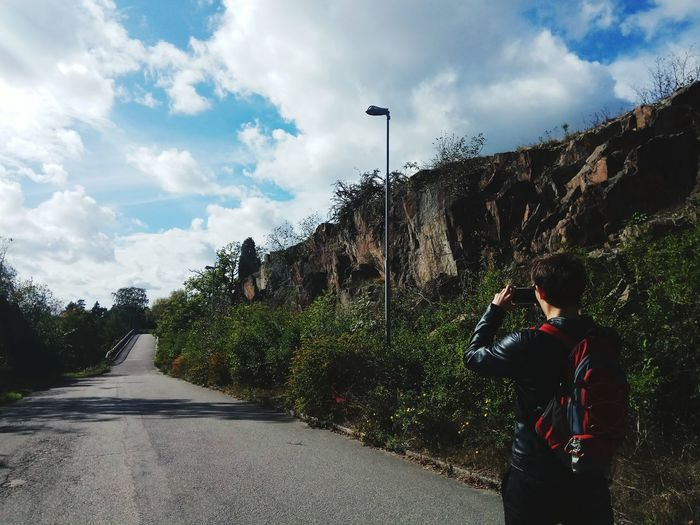 Rear view of man photographing on road against sky