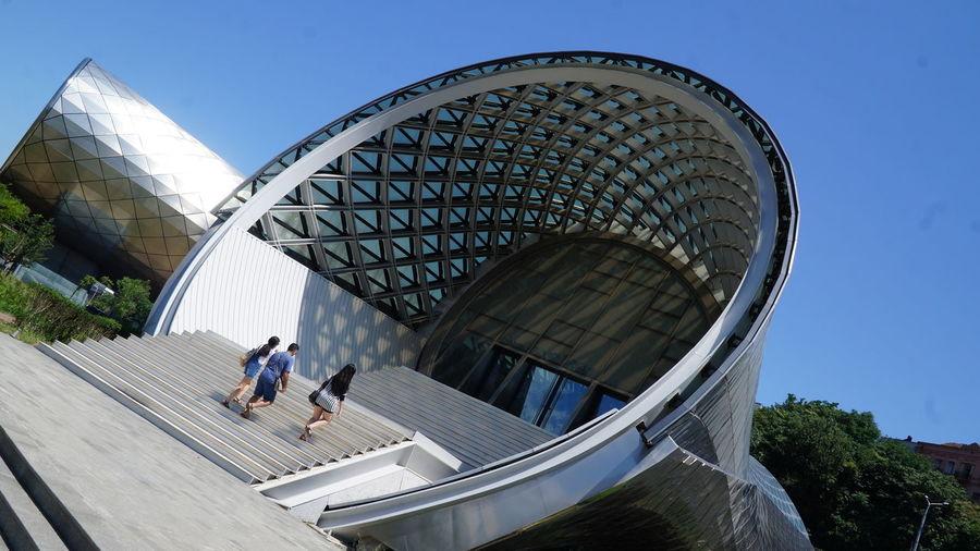 People in modern building against sky