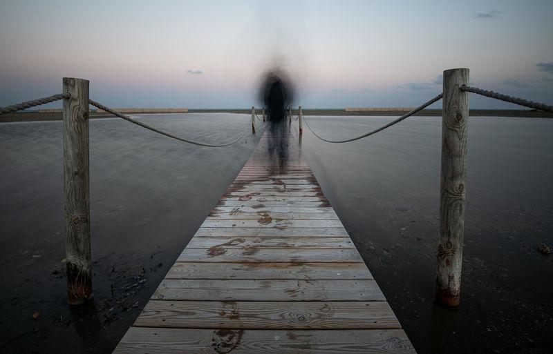 Pier on footbridge against sky during foggy weather