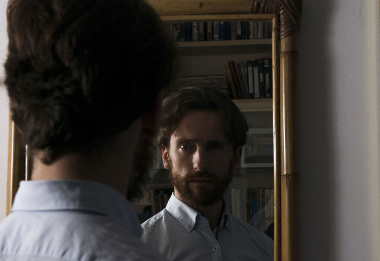 Rear view of confident young man reflecting on mirror at home