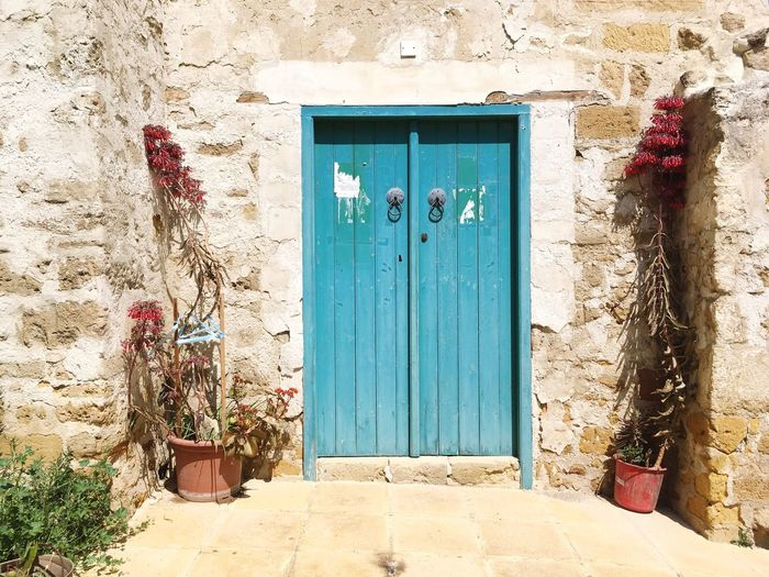 The typical Cyprus entry. Door Architecture Entrance Doorway House Outdoors Built Structure Building Exterior Open Door Typical Wood Doors Stone History Vintage Ceramics Floral Flowers Wall Old Old Buildings Blue Door Blue Entrance Tradition
