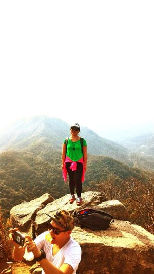 Full length of young woman standing on mountain