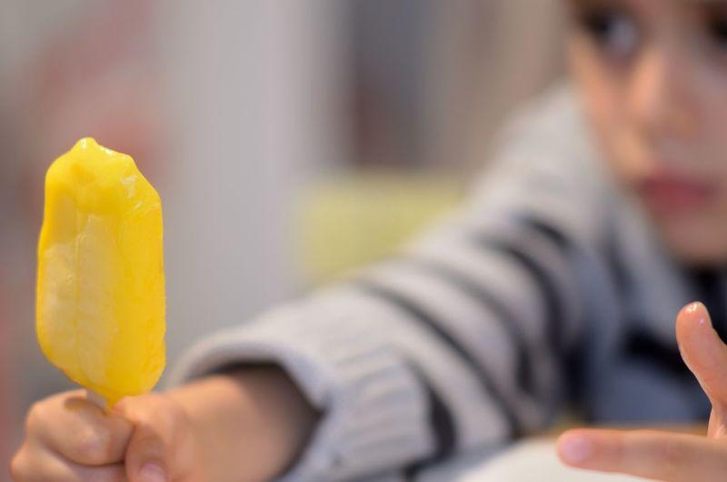 Close-up of boy holding mango ice pop