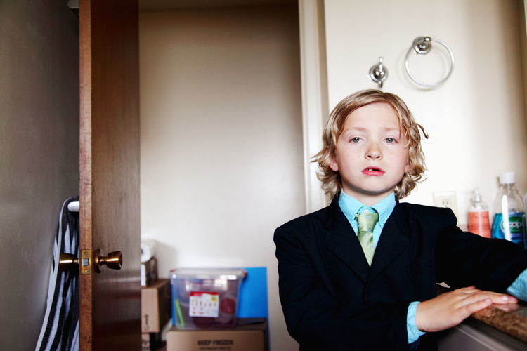 Close-Up Portrait Of Boy Wearing Suit Standing By Door At Home