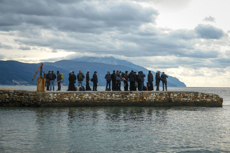 Group of people by sea against sky