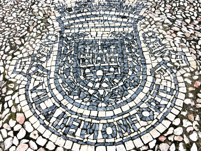 "Calçada portuguesa. ""Portuguese pavement in sidewalk is a traditional-style pavement used for many pedestrian areas in Portugal. It consists of small flat pieces of various different stones, arranged to form a pattern or picture, like a mosaic. It can also be found in Olivença (a disputed territory administered by Spain) and throughout old Portuguese colonies, such as Brazil and Macau. Portuguese workers are also hired for their skill in creating these pavements in places such as Gibraltar. Being usually used in sidewalks, it is in squares and atriums that this art finds its deepest expression."" in Wikipedia (https://en.wikipedia.org/wiki/Portuguese_pavement, 2016-12-27, 00:41) Backgrounds Calçada Portuguesa Circle Close-up Coat Coat Of Arms Coat Of Arms Day Full Frame High Angle View Monforte No People Outdoors Pattern Portuguese Pavement Travel Destinations"