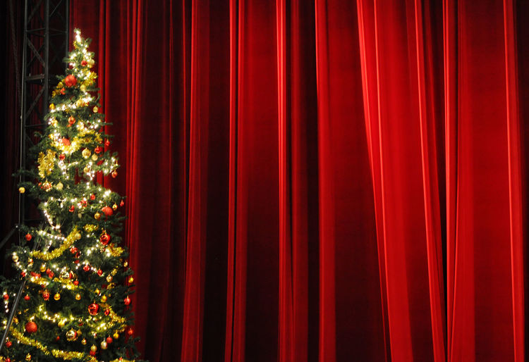 CHristmas tree in front of stage curtains before seasonal concert in theatre in Danang, Vietnam. Abstract Backgrounds Christmas Trees Curtain Danang Decorations Entertainment Events Fabric Hanging Indoors  Pattern Stages Textile Textured  Theatres  Vietnam