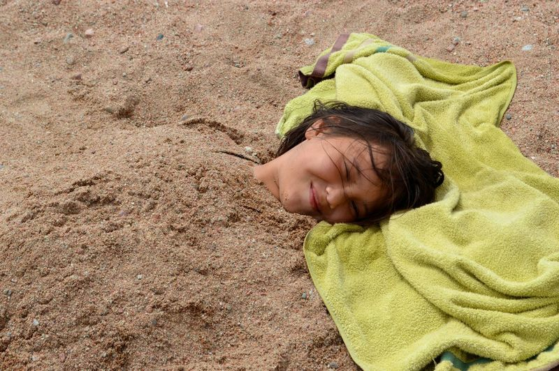 Close-up of girl buried in sand
