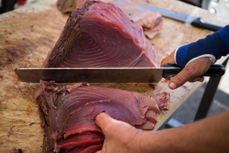 Cropped Image Of Butcher Cutting Tuna