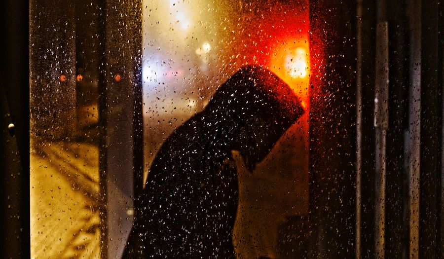Side View Of Young Woman Wearing Raincoat Standing By Wet Window During Rainy Season At Night