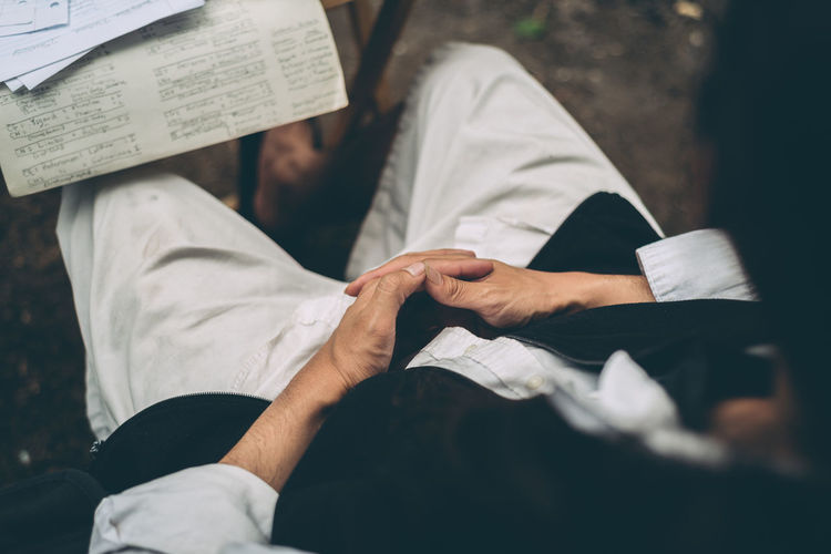 Camping Looking Down Adult Casual Clothing Clasping Hands Hand Holding Hands Human Body Part Human Hand Lifestyles Men Midsection Overhead View Paper Real People Selective Focus Sitting Togetherness