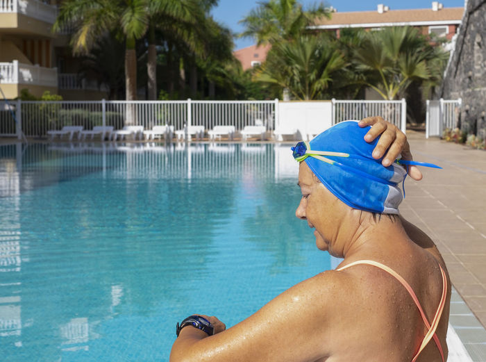 Rear view of senior woman standing by swimming pool