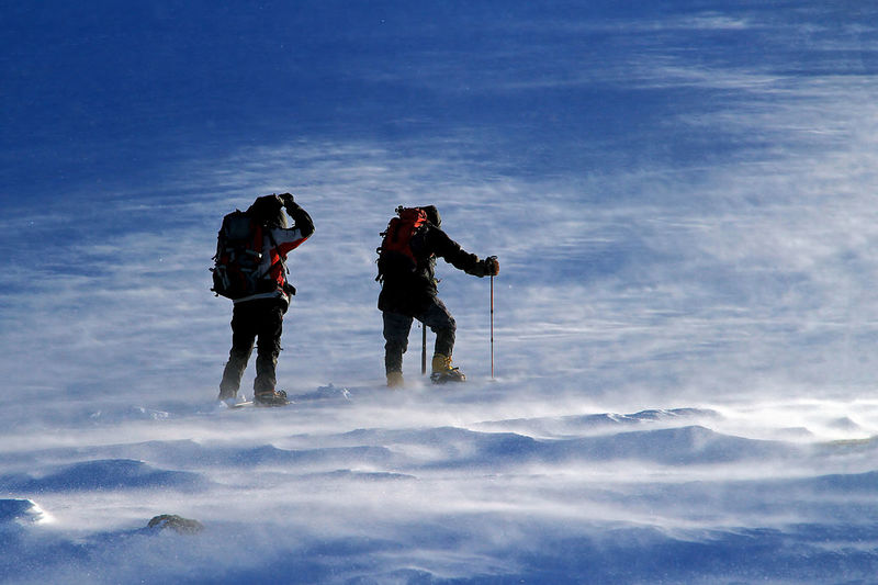 Rear View Of Hikers On Snowcapped Landscape