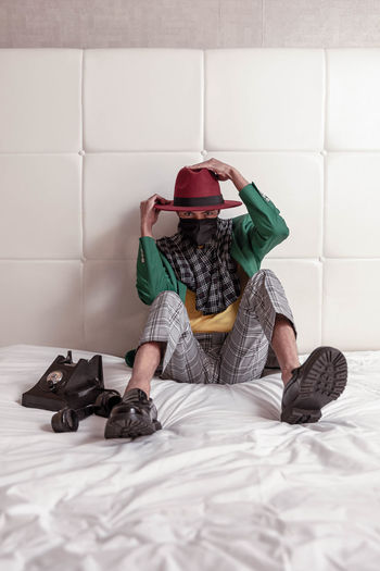 Full length of man sitting on bed against wall