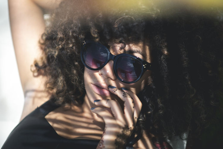 Adult Beautiful Woman Close-up Curly Hair Fashion Front View Glasses Hair Hairstyle Hand Headshot Human Face Indoors  Leisure Activity Lifestyles People Portrait Real People Sunglasses Women Young Adult Young Women