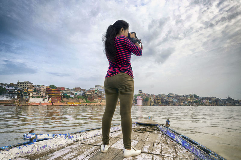 Rear view of woman photographing while standing on boat in river