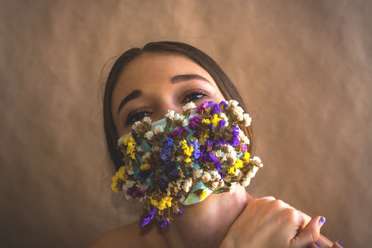 Close-up of woman with flowers on mouth